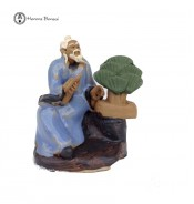 Delightful ceramic creativity figurine holding bonsai snippers and with ceramic bonsai tree.